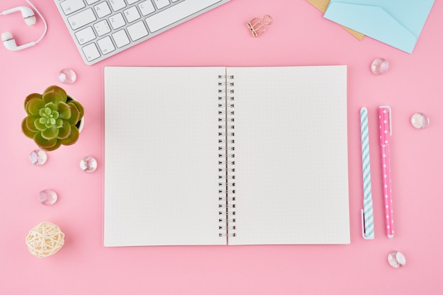 Página de bloc de notas en blanco en el diario de bala en el escritorio de oficina de color rosa brillante. vista superior de la moderna mesa brillante con notebook