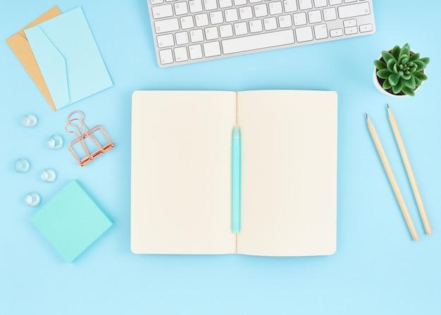 Página de bloc de notas en blanco para texto en escritorio de oficina azul. vista superior del moderno cuaderno de mesa brillante,