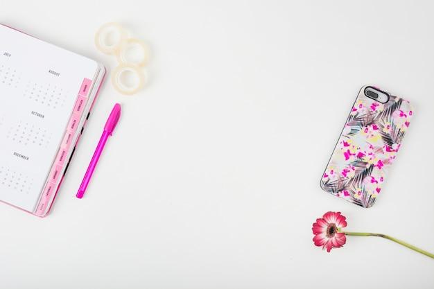 Página de calendario; teléfono inteligente; flor; cinta de pluma y chelo sobre fondo blanco