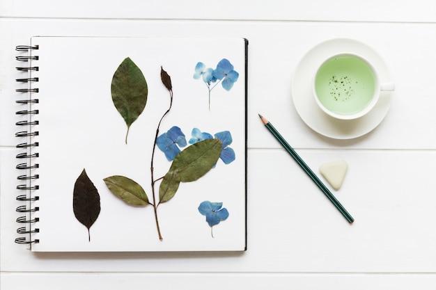 Página con flores secas junto a lápiz.
