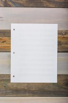 Página musical blanca en blanco pegada en la pared de madera