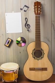 Página musical en blanco; casete; disco compacto; y nota musical pegada en pared de madera con guitarra y bongo drum.