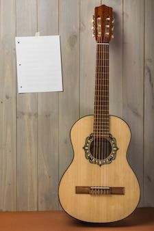 Página musical en blanco sobre pared de madera con guitarra.