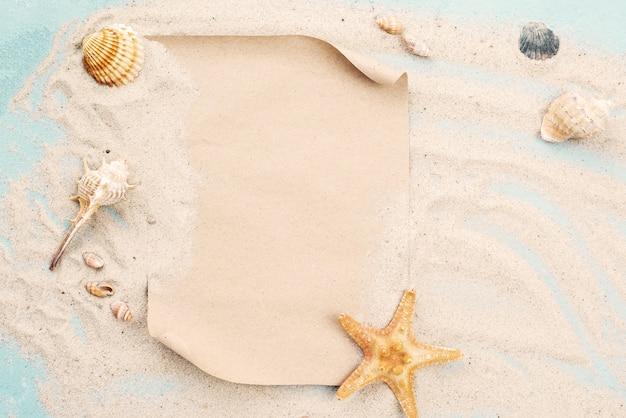 Página de papel en blanco sobre arena con conchas