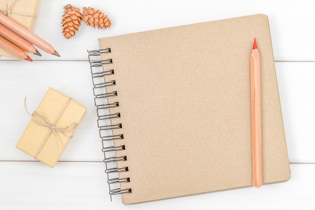 Página vacía del cuaderno para escribir con lápices, caja de regalo y conos sobre fondo blanco de madera