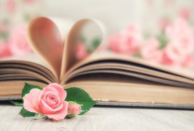 Páginas de un libro viejo curvado en un corazón y rosas.
