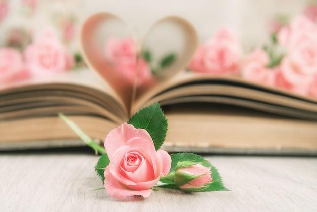 Páginas de un viejo libro curvadas en un corazón y rosas.