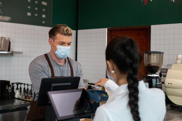 Pago sin contacto con teléfono móvil para pagar dinero con máquina de pago. compra de café con teléfono inteligente con sin contacto. máquina de sujeción de barista de café para el costo del servicio pagado por el cliente.