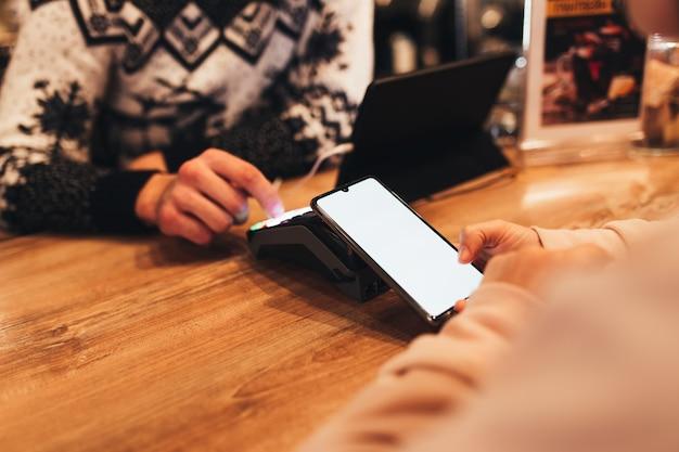 Pago sin efectivo con nfc y teléfono en una terminal de café
