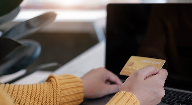 Pago en línea, manos de joven usando computadora y mano sosteniendo tarjeta de crédito para compras en línea