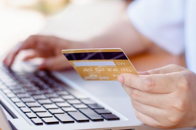 Pago en línea . manos de mujer sosteniendo tarjeta de crédito y usando laptop. las compras en línea