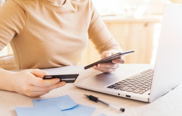 Pago en línea, manos de mujer sosteniendo teléfono inteligente con tarjeta de crédito para compras en línea