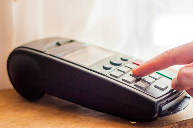 Pago con tarjeta de crédito - hombre de negocios explotación pos terminal. tarjeta de pago en un terminal bancario. el concepto de pago electrónico. código de pin de mano en el pin pad de la máquina de tarjeta o pos terminal