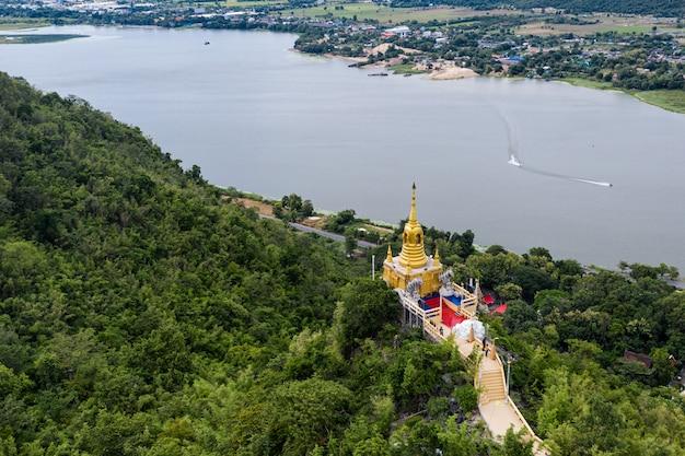 Pagoda dorada en la colina en la selva tropical en wat ban tham