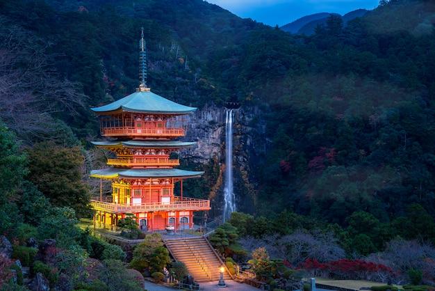 Pagoda seigantoji en el templo santuario kumano nachi taisha con cascadas nachi a la vista en la temporada de otoño, el famoso y popular lugar turístico por la noche en wakayama, japón.