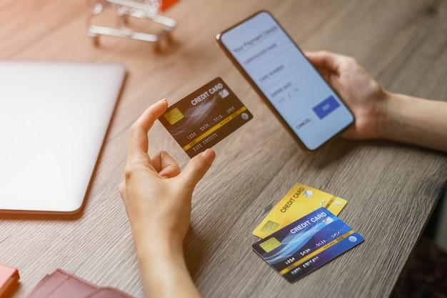 Pagos móviles. manos usando teléfono inteligente y tarjeta de crédito para compras en línea.