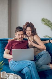 Pagos online. linda pareja joven planeando comprar algo en línea