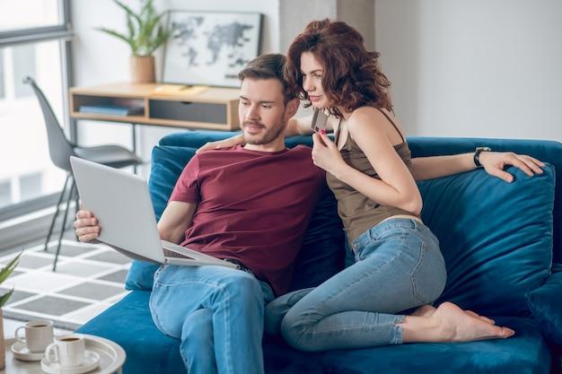 Pagos periódicos. pareja haciendo pagos periódicos en línea y mirando involucrado