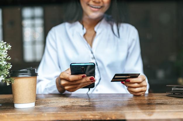 Pague los productos con tarjeta de crédito a través de un teléfono inteligente en una cafetería.