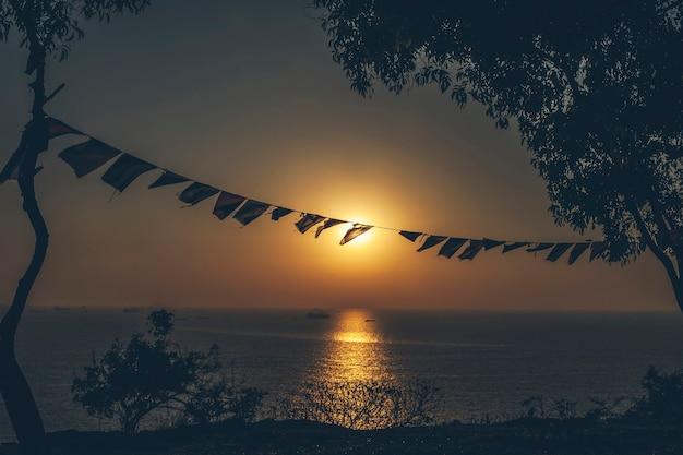 El paisaje está abierto con vistas al mar y árboles con banderas festivas ondeando al viento.