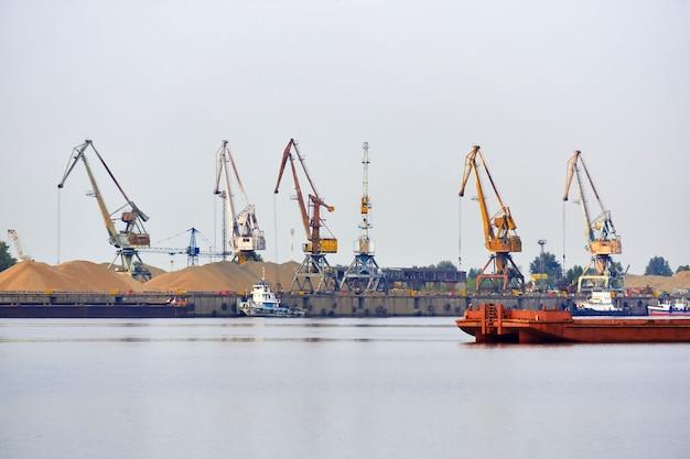 Paisaje acuático fluvial industrial con terminal de carga y amarre de remolcadores y barcazas a granel