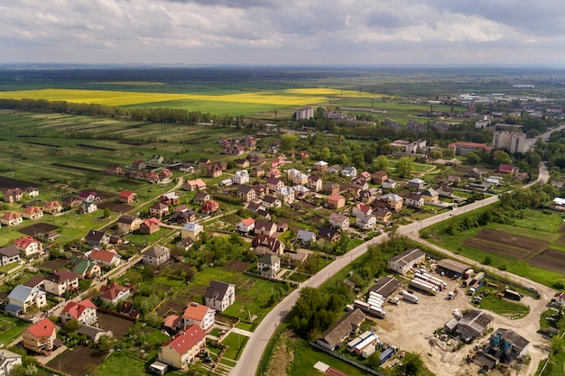 Paisaje aéreo de una pequeña ciudad o pueblo con hileras de casas residenciales y árboles verdes.