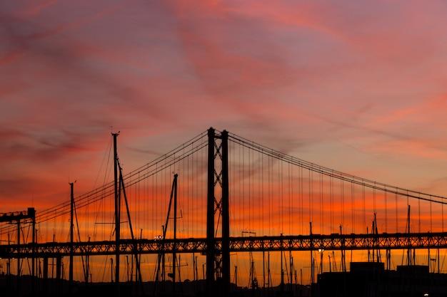 Paisaje al atardecer en la ciudad con puente y yates