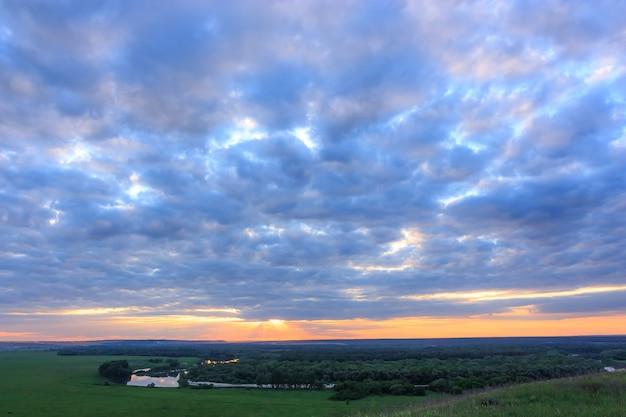 Paisaje al atardecer con un maravilloso cielo dorado y rosado, increíbles nubes púrpuras en la noche durante la puesta de sol sobre campos verdes y un río sinuoso