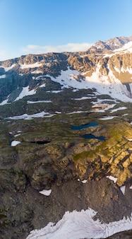 Paisaje alpino de gran altura con majestuosas cumbres rocosas. panorama aéreo al amanecer. alpes, andes, himalaya concepto
