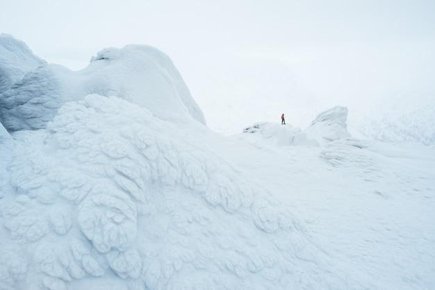Paisaje blanco como la nieve con un escalador en las montañas. pintoresca escarcha sobre rocas en la niebla
