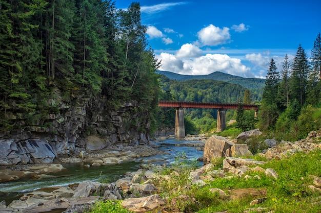 Paisaje de los cárpatos, montañas, árboles, río y puente contra el cielo azul