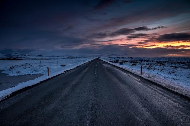 Paisaje de una carretera en el campo durante la puesta de sol