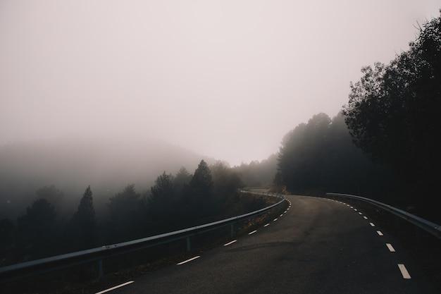 Paisaje de carretera con curvas de niebla en la montaña
