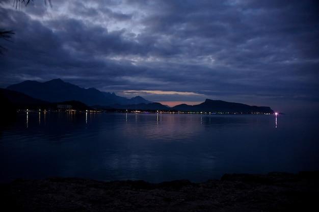 Paisaje de la ciudad en la playa diferente en la noche al pie de la montaña