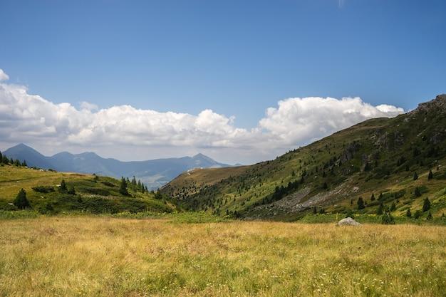 Paisaje de colinas cubiertas de vegetación con montañas rocosas bajo un cielo nublado