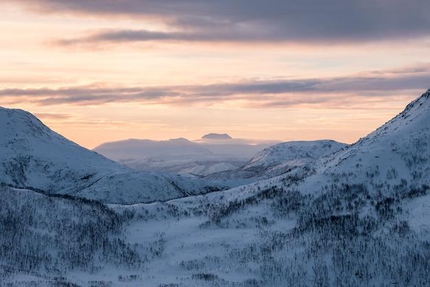 Paisaje cordillera nevada con cielo colorido en el pico al amanecer.
