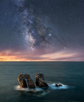Paisaje costero en la noche con el mar y la vía láctea en el cielo