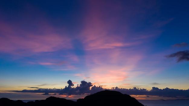 Paisaje del crepúsculo, cielo azul y tono pastel con silueta de montaña en primer plano en la vista aérea del mar