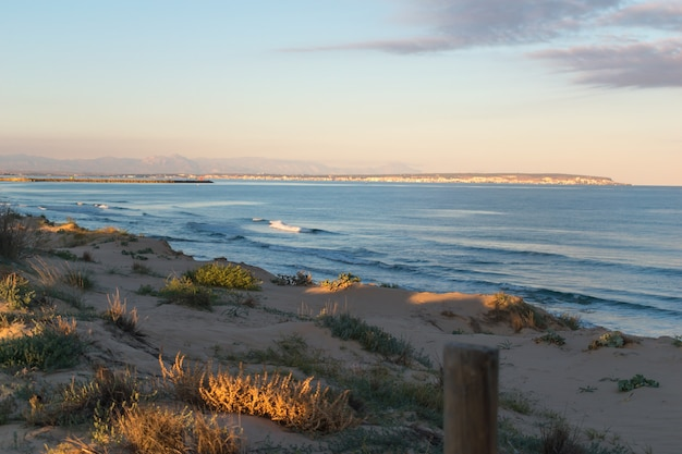 Paisaje de dunas de arena en la playa al atardecer cerca del mar con nubes oscuras en el cielo y pueblo en el fondo