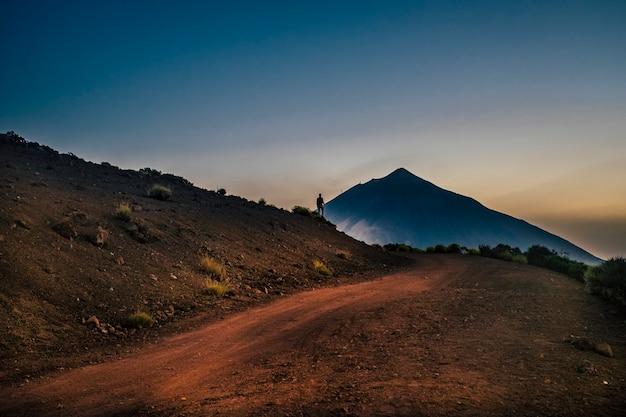 Paisaje escénico con hombre de pie frente a la montaña.