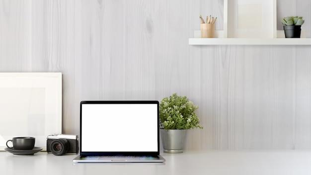 Paisaje del escritorio de oficina con el ordenador portátil de la pantalla en blanco de la maqueta. espacio de trabajo mínimo