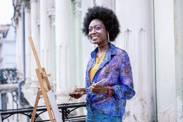 Paisaje exterior. artista radiante hermosa elegante que se siente feliz mientras pinta el paisaje exterior