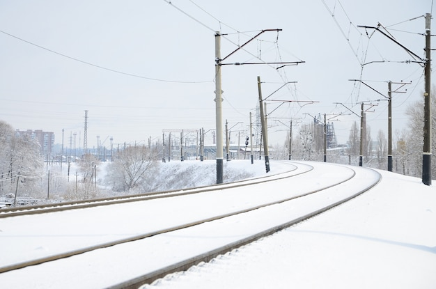 Paisaje ferroviario de invierno, pistas ferroviarias en el país industrial cubierto de nieve.