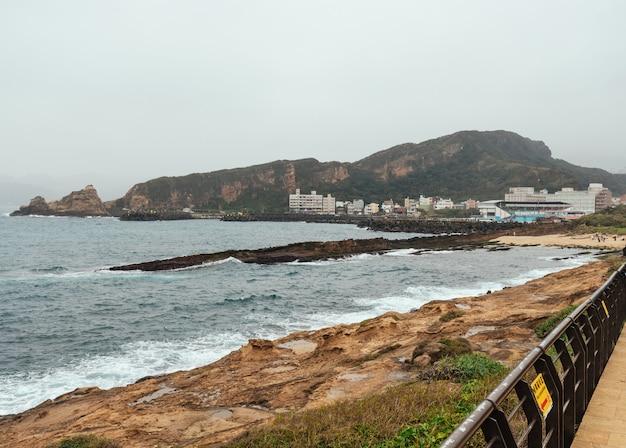 Paisaje del geoparque yehliu, un cabo en la costa norte de taiwán. un paisaje del mar con edificios de la ciudad.