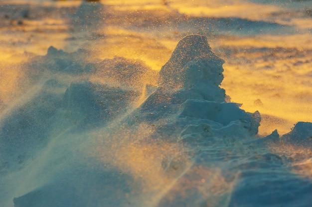 Paisaje helado ilimitado durante una tormenta de nieve en la puesta del sol en invierno.