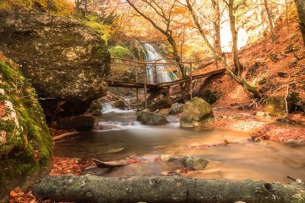 Paisaje con hermosa cascada y el pequeño puente en primer plano.