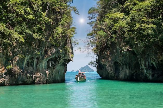 Paisaje hermoso de la montaña de las rocas y del mar cristalino con el barco del longtail en phuket, tailandia.