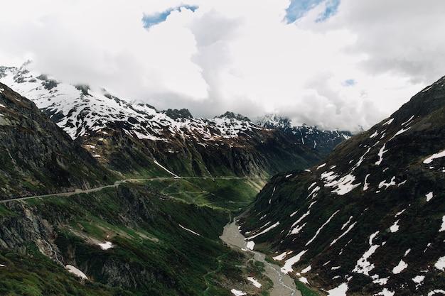 Paisaje hermoso de las montañas de los alpes en tiempo nublado del verano