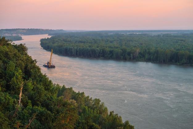 Paisaje hermoso del río con las orillas verdes y nave con el espacio de la copia.