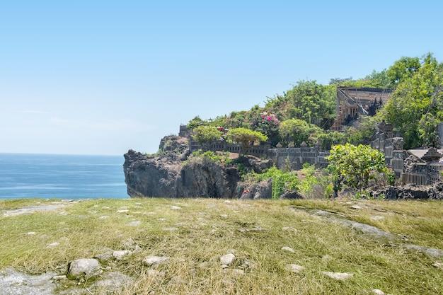 El paisaje de hierba verde y rocas en el acantilado con paisaje marino